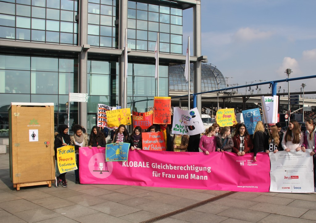 students in front of a toilet in Berlin during  International Women's Day